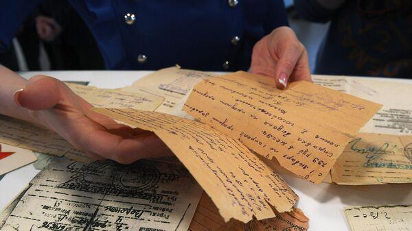 Фронтовые письма времён Великой Отечественной войны в руках посетительницы пункта приема документов для проекта Дорога памяти во флагманском информационном центре ВДНХ в Москве