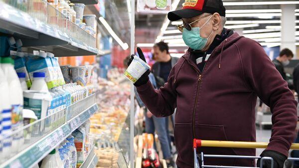 Мужчина в защитной маске покупает продукты в гипермаркете