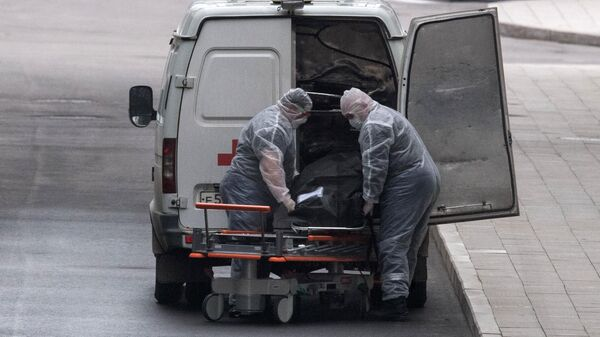 Медицинские работники перевозят тело умершего на территории карантинного центра в Коммунарке