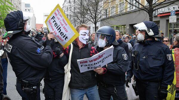Полиция задерживает демонстранта во время акции протеста против карантинных мер в связи с коронавирусом в Берлине