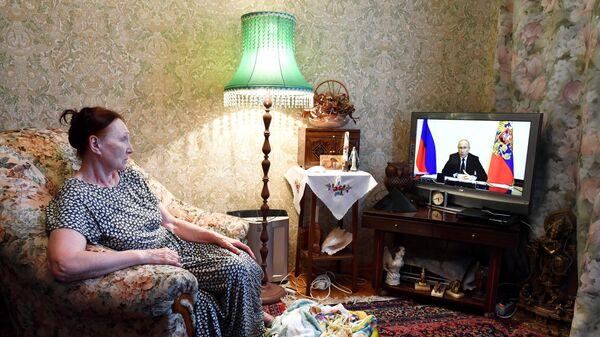 Жительница Москвы смотрит трансляцию совещания президента РФ Владимира Путина с главами регионов по борьбе с распространением коронавируса
