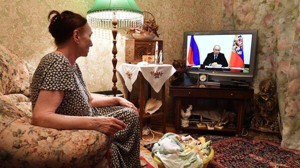 Жительница Москвы смотрит трансляцию совещания президента РФ Владимира Путина с главами регионов по борьбе с распространением коронавируса в России