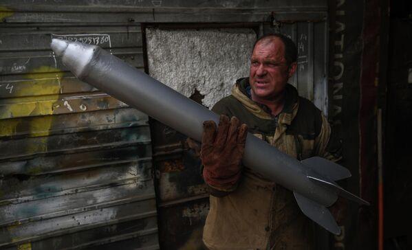 Мастер Максим Свекла держит в руках муляж снаряда для изготовления копии боевой машины Катюша в гараже своего дома в селе Большой Оеш Новосибирской области