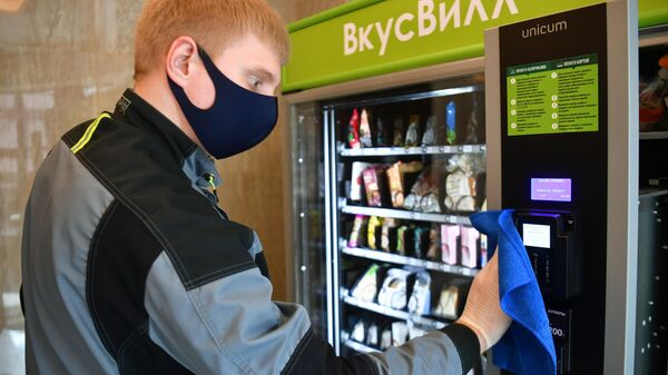 Сотрудник сетевого магазина продуктов питания ВкусВилл проводит санитарную обработку вендингового автомата