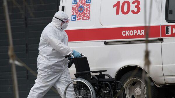 Медик везет инвалидное кресло к машине скорой медицинской помощи, доставившей пациента в карантинный центр в Коммунарке