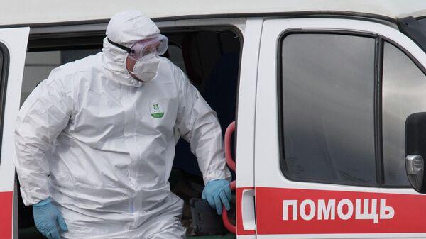 Медик выходит из машины скорой медицинской помощи на территории карантинного центра в Коммунарке