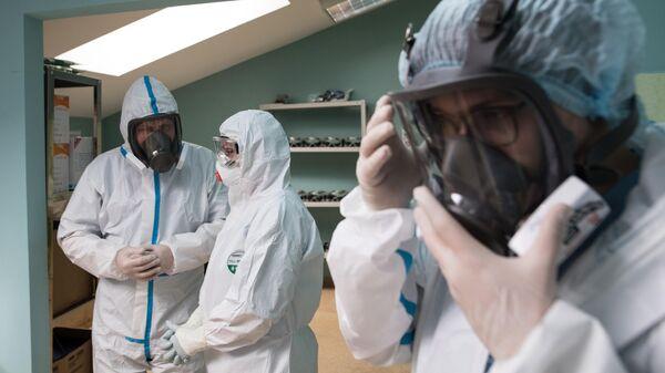 Медицинские работники одевают защитные костюмы и маски в стационаре для больных с коронавирусной инфекцией