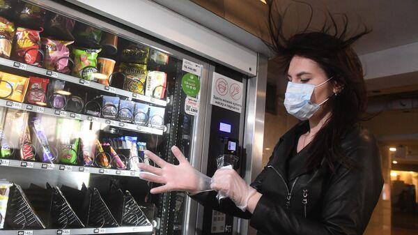 Девушка демонстрирует набор индивидуальных средств защиты, купленный в вестибюле станции Московского метрополитена