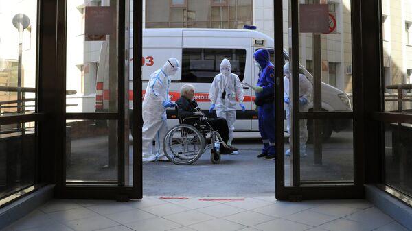 Медицинские работники и пациент в стационаре для больных с коронавирусной инфекцией на базе Медицинского научно-образовательного центра МГУ