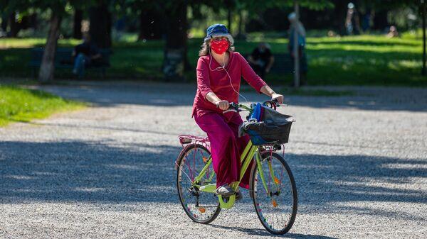 Женщина на велосипеде в одном из парков Милана