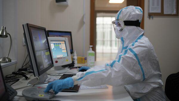 Врач смотрит показания аппарата компьютерной томографии во время обследования пациента в госпитале для зараженных коронавирусной инфекцией COVID-19 в центре МГУ имени М. В. Ломоносова