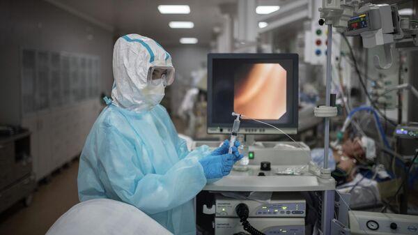 Врач во время бронхоскопии у пациента в отделении реанимации и интенсивной терапии госпиталя для зараженных коронавирусной инфекцией COVID-19 в центре МГУ имени М. В. Ломоносова