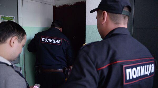 Сотрудники полиции стоят у двери квартиры в жилом доме