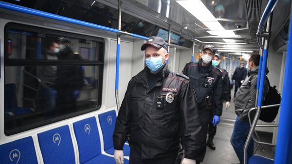 Сотрудники полиции в защитных масках в вагоне московского метро