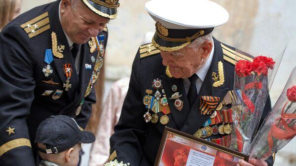 Ветеран Великой Отечественной войны Лука Иванович Кузин принимает поздравления во время персонального парада во дворе своего дома в Севастополе
