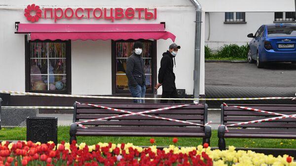 Мужчина в защитных масках возле цветочного магазина на одной из улиц Москвы