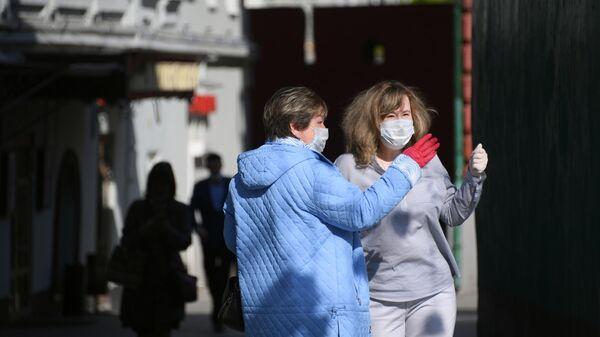 Женщины в медицинских масках и перчатках на одной из улиц в Москве