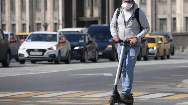 Мужчина на самокате на одной из улиц в Москве