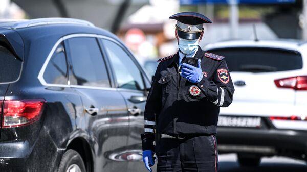 Сотрудник дорожно-патрульной службы ГИБДД во время проверки наличия пропуска у водителя на блокпосту на пересечении Варшавского шоссе с МКАД