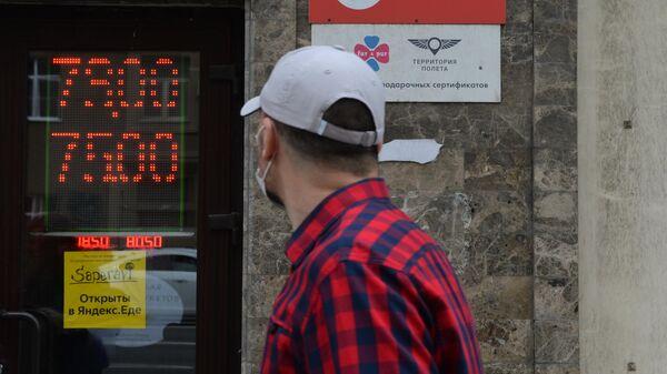 Мужчина в защитной маске у информационного табло с курсом валют на Тверской улице в Москве