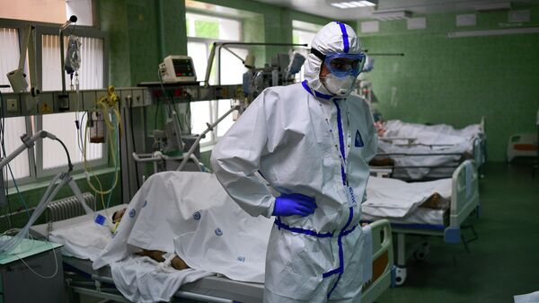 Врач и пациенты в отделении реанимации и интенсивной терапии городской клинической больницы имени В. В. Виноградова, переоснащенной для лечения пациентов с  COVID-19