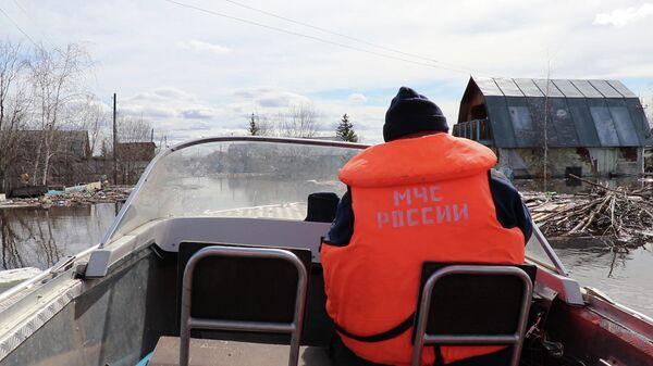 Сотрудник МЧС РФ на катере в поселке Кангалассы