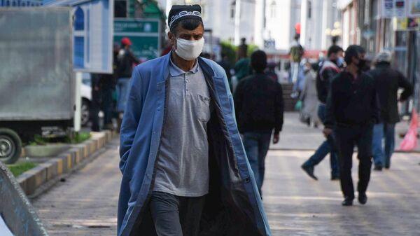 Мужчина в защитной маске на одной из улиц в Душанбе