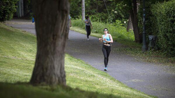 Девушка во время пробежки в парке Валентино в Турине