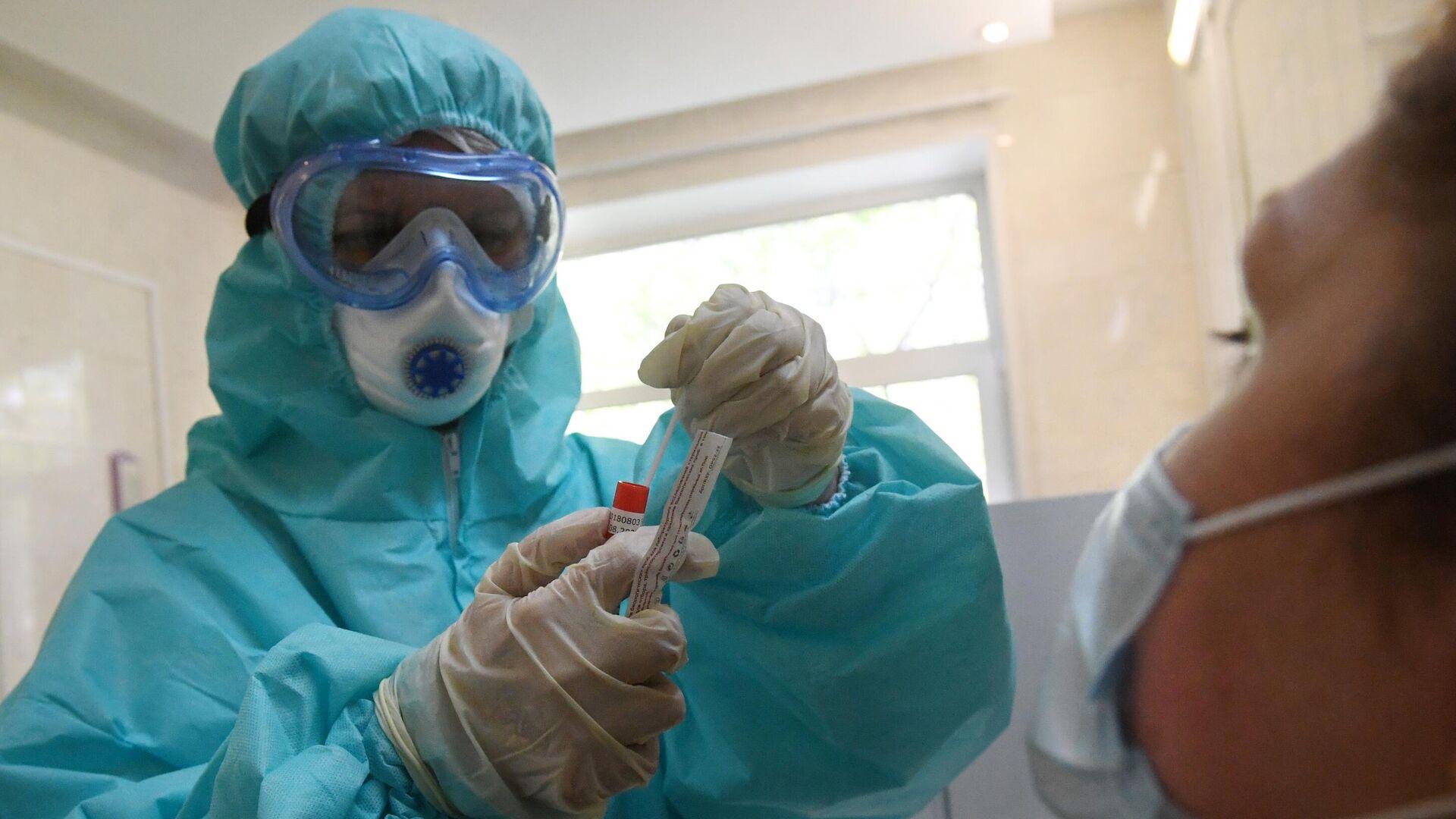 Медицинский работник в защитном костюме проводит забор биоматериала для анализа на коронавирус в городской поликлинике Москвы - РИА Новости, 1920, 14.06.2021