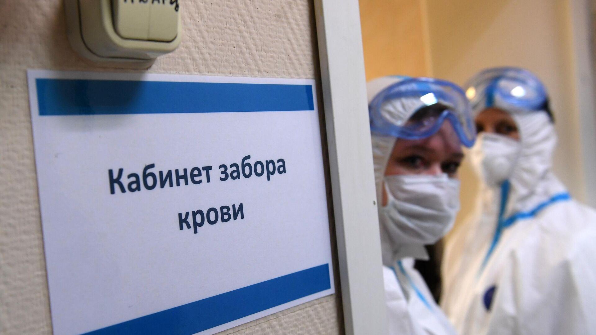 Медицинские работники в защитных костюмах у кабинета забора крови на наличие антител к COVID-19 в городской поликлинике Москвы - РИА Новости, 1920, 04.06.2020