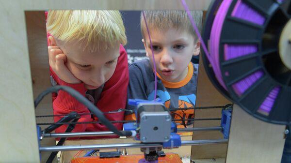 Дети наблюдают за работой 3D-принтера