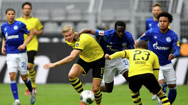 Dortmund's Norwegian forward Erling Braut Haaland (Center L) vies for the ball with Schalke's Senegalese defender Salif Sane during the German first division Bundesliga football match BVB Borussia Dortmund v Schalke 04 on May 16, 2020 in Dortmund, western Germany as the season resumed following a two-month absence due to the novel coronavirus COVID-19 pandemic. (Photo by Martin Meissner / POOL / AFP) / DFL REGULATIONS PROHIBIT ANY USE OF PHOTOGRAPHS AS IMAGE SEQUENCES AND/OR QUASI-VIDEO