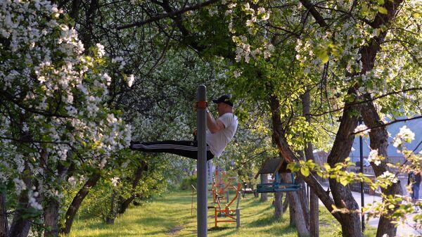 Мужчина занимается спортом на общественном тренажере на набережной Енисея в Дивногорске Красноярского края