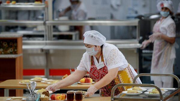 Работница школьной столовой разносит тарелки с едой