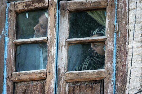 Местные жители выглядывают из окна своего дома в Шринагаре, Кашмир