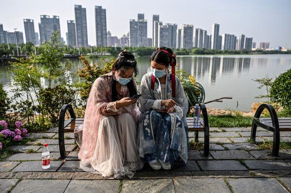 Девушки в масках и традиционных костюмах династий Сун и Тан в парке в Ухане, Хубэй