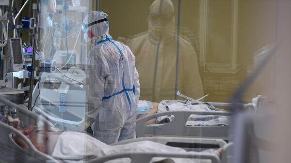 Медицинский работник возле кровати пациентов в одном из отделений госпиталя COVID-19 в Центре мозга и нейротехнологий ФМБА России