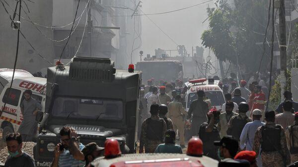Автомобили скорой помощи и пожарной службы в районе крушения пассажирского самолета в жилом районе недалеко от аэропорта в Карачи