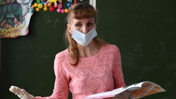 Учительница в защитной маске ведет урок  в общеобразовательной школе