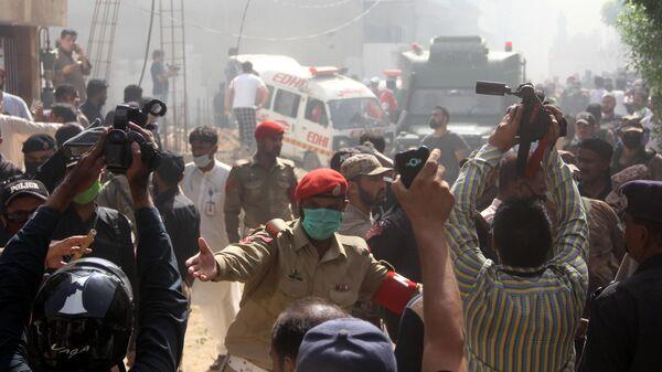 Журналисты и сотрудники полиции на месте крушения пассажирского самолета Airbus A-320 авиакомпании Pakistan International Airlines (PIA) в Карачи