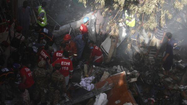Сотрудники специальных служб извлекают тела погибших на месте крушения пассажирского самолета Airbus A-320 авиакомпании Pakistan International Airlines (PIA) в Карачи