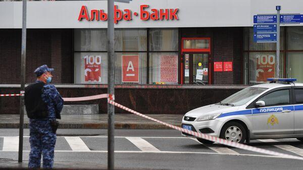 Сотрудник полиции в оцеплении у отделения Альфа-банка в центре Москвы, откуда поступило сообщение, что неизвестный удерживает несколько человек и угрожает взорвать отделение
