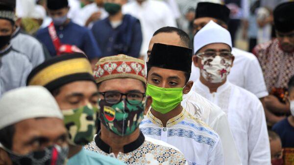 Верующие в защитных масках у мечети Аль-Машун в провинции Северная Суматра в Индонезии