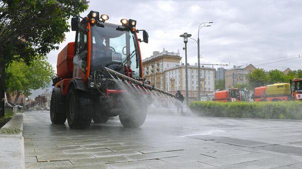 Автомобиль коммунальных служб во время дезинфекции тротуаров в Москве