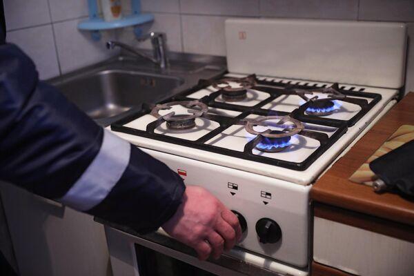 Сотрудник газовой службы проверяет газовую плиту на наличие неисправностей