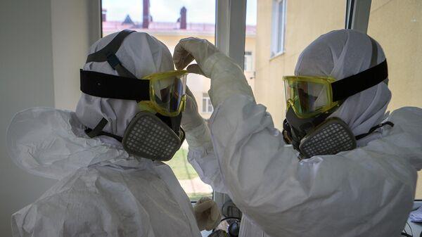 Медицинские работники одевают средства индивидуальной защиты перед входом в красную зону в госпитале для зараженных коронавирусной инфекцией COVID-19 в Черкесске