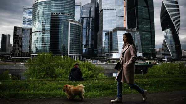 Девушка гуляет с собакой на набережной Тараса Шевченко в Москве