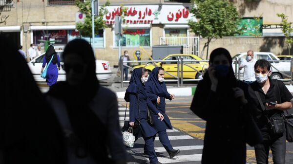 Прохожие в защитных масках на улице Тегерана