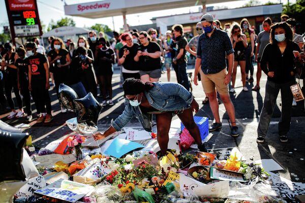 Люди  у импровизированного мемориала в честь афроамериканца Джорджа Флойда на месте его гибели
