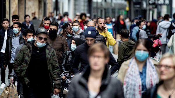 Люди гуляют по главной торговой улице Рю Нев в центре Брюсселя. 16 мая 2020 год